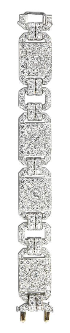 DIAMOND BRACELET, CIRCA 1920.  Composed of four rectangular plaques pierced in a geometric pattern, alternating with square links millegrain set with circular- and single-cut diamonds, length approximately 167mm.