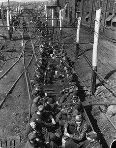 "Mining Town/ Pa. The 2:45 p.m shift of coal miners riding in coal cars as they head into the mountain for the ""face"" (work area) in the pits, a good 45 minutes from loading spot, which means they spend an hour and half or two hrs a day in the mines for which they do not  