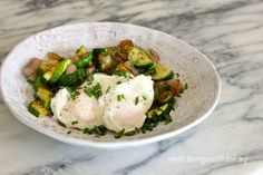 Poached Eggs over Zucchini Hash:  2 small zucchini, cut in half lengthwise and sliced 1/4″ thick OR shredded     2 small shallots, peeled and thinly sliced 4 eggs (cook eggs in two batches) sea salt (I use Maldons Sea Salt) pepper chives, sliced 1/3 parmesan cheese, freshly grated (optional) 2 T butter, ghee or coconut oil 1 T white distilled vinegar.