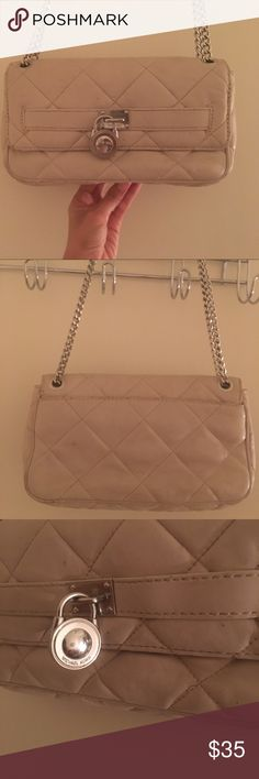 MK quilted flap shoulder bag! Michael Kors chain medium size bag. Color is cream/ grey. Has quilted leather exterior. Crome silver tone chain that could be a shoulder or cross-bag. Center hardware lock with MK logo. Interior is beige with signature logo.