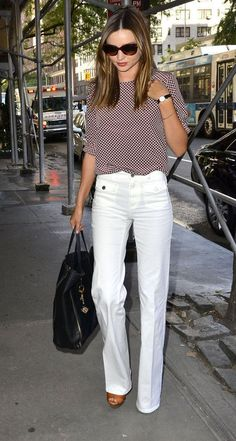 Stylish and crisp white trousers, satin patterned blouse top, black bag