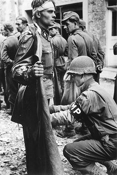 "An SS soldier of Panzergrenadier Division ""Götz von Berlichingen"") disguised as a civilian is frisked by a US MP of the 2d Armored Division. Caen, Normandy, France. Photograph by Robert Capa. 1944"