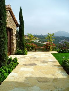 Lemon tree in pot with red flowers tuscan, stone, flagstone motorcourt - mediterranean - Landscape - San Diego - The Design Build Company