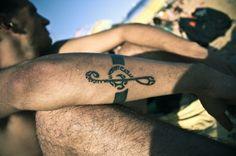 Nota musical tatuada en brazo