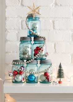 This Mason Jar Christmas Tree is perfect for a mantel or entry table. Fill six like-sized canning jars with ornaments, tinsel, greenery, you name it. Assemble the jars in a pyramid, then wrap it with a shiny garland and top with a star. Done! - CountryLiving.com