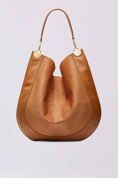 This modern hobo bag is finished in irresitably soft calf hair and leather, and accented with sleek gold hardware. It has a leather strap and magnetic snap closure.