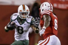 Miami running back Duke Johnson (8) runs past Nebraska safety Corey Cooper (6) in the first half of an NCAA college football game in Lincoln, Neb., Saturday, Sept. 20, 2014.