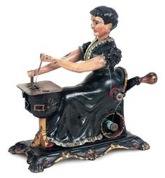 "Very rare cast iron mechanical toy lady at a sewing machine. She holds a lever in each hand, under her seat is a hidden spool of thread that is attached to the machine through her arm. When the wooden handled lever at the back is turned, the woman nods her head back and forth, and moves her arms as though sewing. The toy is painted its original black with gilt and aqua finish. The number ""162"" in impressed on the top plate of the sewing machine. Circa 1875."