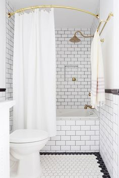 Small monochrome bathroom with subway tile and gold accents