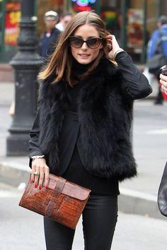 Olivia Palermo sports a black fur vest, Hermes exotic skin clutch, and pristinely polished red fingernails.