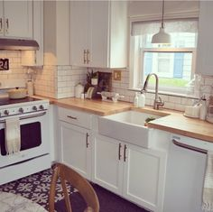 Kitchen white appliances subway tile farmhouse sink wood countertop  Dumb waiter in corner to put food to the badement
