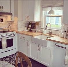 Kitchen white appliances subway tile farmhouse sink wood countertop