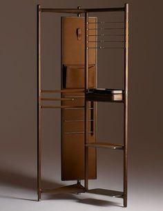 """Hermès Launches a Collection of Exquisite Furnishings Designed by Philippe Nigro The Groom valet is a stunning metal structure covered in Canaletto walnut. Its rotating mirror is backed in leather and equipped with a hook and a pocket, while stainless-steel bars and leather shelving provide additional storage. It measures 36"""" w. x 21.5"""" d. x 75.5"""" h.; $45,100."""