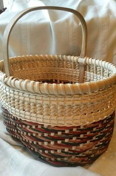 This is a beautiful, large basket woven in fall colors. The decorative natural weaving at the top was created using two types of ti twining. Featuring a solid wood bottom and handle, it is very strong and sturdy. The fall colors basket is in stock. The blue colors basket (or any
