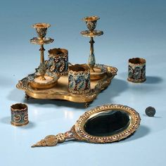 Collection of French vanity items consisting of eight pieces of French dore bronze champleve including pair of candlesticks, footed vanity tray with onyx inset four graduated canisters and a hand mirror, c.1890, eight pieces
