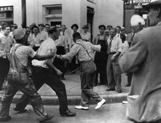 "A photographer (right) captures a white mob assaulting an African American man during the Detroit ""race riot,"" June 22, 1943."