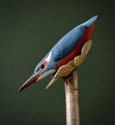 One-piece carving of a kingfisher diving through autumn leaves. From a coppice hazel block stick. Mainted with acrylics and finished with acryilic varnishes