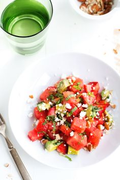A refreshing summer strawberry watermelon feta salad with mint that's has strawberries, watermelon, savory feta cheese, creamy avocados, basil and almonds!