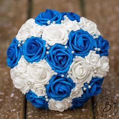 """""""Pearly Blue"""" Royal Blue and White Bridal Wedding Bouquet with Scattered Pearls Simple yet detailed and perfectly elegant! This royal blue and white bouquet is stealing hearts this year! With pearls strategically placed throughout the bouquet, it is the perfect addition to your wedding day. Our signature Soft Touch roses come in many different colors to match your color palette perfectly! Bottom is lined with royal blue organza tulle, and handle is wrapped in royal blue ribbon. Listed: One…"""