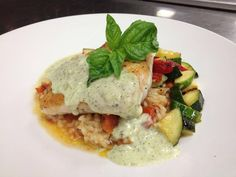 Pan seared corvina with a roasted tomato risotto, roasted zucchini and peppers with a pesto cream.