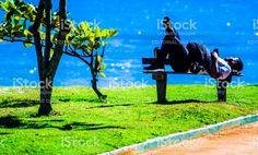 Homem sozinho repousa deitada em um banco na praia do Perequê em Ilhabela, Brasil, em uma manhã ensolarada. foto royalty-free