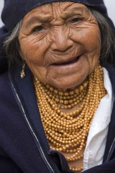 The native people traditionally wear gold painted beads. The number of strands signifies wealth. They actually make gold dust, combine it with lacquer and paint the beads! Otavalo, Ecuador.