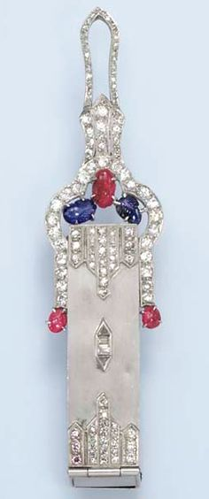 "AN ART DECO DIAMOND, RUBY AND SAPPHIRE LIPSTICK CASE  Of rectangular outline, decorated by single, baguette and triangular-cut diamonds, the cabochon ruby pushpiece sliding open to reveal a lipstick, to the circular and single-cut diamond surmount, enhanced by carved ruby and sapphire leaves, mounted in platinum and white gold, (inscribed ""To Mae From Jim""), circa 1925"