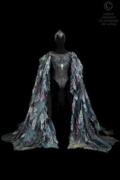 Opera National de Paris ROLE: Rothbart ARTISTS: Rudolf Noureev DESCRIPTIF COSTUME: Jerkin napina black, decorated with a bird motif on the chest, long argyle green lycra and napina black sleeves. Cloak band Crystal various colors (gray, purple green ...) lined with tulle and worked on upside down braid horsehair. The whole is covered with crystal the same colors, cut into leaf pattern, the edges and the ribs are embellished with embroidery to the green wire.