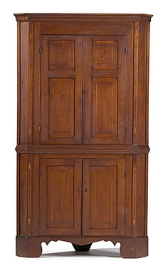 Kentucky, early 19th century. An inlaid corner cupboard in walnut with pine and poplar secondary, the upper section with molded cornice over double inset paneled doors, the lower section with one shelf behind paneled doors, all over a shaped apron and bracket feet; ht. 79.5, wd. 44, dp. 18.5, corner 22.5 in.