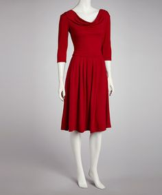 A posh frock is found with pleats below the waistline and a draping neckline. Three-quarter sleeves and pockets at the hips create a show-stopping piece.