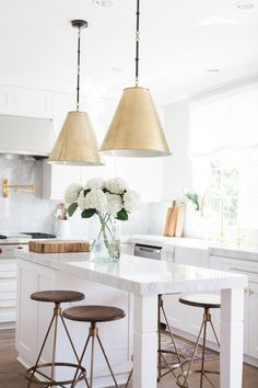 Elegant marble all white kitchen with gold details and lighting