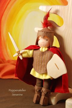This is Saint George. He fights the dragon to save the princes. He can not be missed on the seasonal table in September when Michaelmas is coming up on the 29th. This doll is made of made of wool felt, velours and cotton flanel. The sword and the shield are hand sawn wood. The doll is 21cm (8.4 inch) high and approx.15cm (6 inch) wide. Saint George is a knight, so is Saint Martin. This knight could also represent Saint Martin.  This doll cannot stand on its own, it needs something to lean…