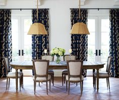 Grand Symmetrical Dining Room Deep blue curtains flank French doors.  The dining table in the 2011 Princess Margaret Showhome was chosen for its oval ends and the extra leaf. Burlap pendants hung low create a relaxed intimacy.