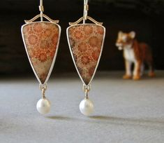 Betsy Bensen: earrings of fossilized coral, pearl, 14kt gold, and sterling silver