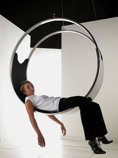 """The Ring Hanging chair is a peaceful place in which to sit, relax, swivel or read. Features a 100% Italian leather seat cushion in black and a solid stainless steel base. Measures: 51"""" wide x 41"""" high x 19.7"""" deep Please allow 3-4 weeks for shipping."""