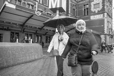 Two women walking in the rain near Amsterdam Central Station - Steppeland Street Photography