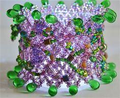 "Sophie's Vineyard Bracelet -  Designed using Free Form Peyote Stitch. Shimmering purple Seed Beads form the base of this netted bracelet, embellished with Czech crystals and lined with green tear-drop crystals. The double-beaded closure blends for a seamless finish on this reversible piece of art. Bracelet measures 6 ½"" long by 2 ½"" wide."