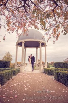 Bride and groom kiss under pagoda at Froyle Park wedding photographs. Photography by one thousand words wedding photographers