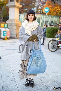 20-year-old Ume on the street in Harajuku wearing a Sou Sou coat with an Issey Miyake skirt, Dr. Martens shoes, and a Hunting World bag.