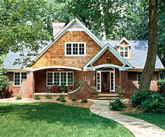 After - The new double-gabled entry -- its combination of two-tone brick cladding and cedar siding -- serves as a focal point and frames the enlarged foyer of the revived ranch. Stone forms the walks and stairs, and larger windows supply cottage charm.