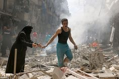 People walk amid the rubble of destroyed buildings following a reported air strike on the ...