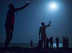 Searching for Signals Photograph by John Stanmeyer, National Geographic  Impoverished African migrants crowd the night shore of Djibouti city, trying to capture inexpensive cell signals from neighboring Somalia—a tenuous link to relatives abroad. For more than 60,000 years our species has been relying on such intimate social connections to spread across the Earth.