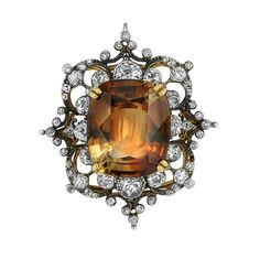 Antique Silver, Gold, Topaz and Diamond Pendant-Brooch   Centering one cushion-shaped topaz approximately 17.75 cts., framed and quartered by 16 old-mine and old European-cut diamonds approximately 1.95 cts., within an openwork diamond-set scroll design, approximately 9.4 dwt. Victorian or Victorian style