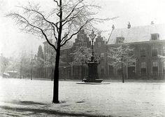 Winter in Utrecht: 1910. Besneeuwde Neude met pomp. Huizenrij waar nu het (voormalig) postkantoorgebouw staat. Links de Vinkenburgstraat