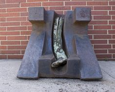 This sculpture is titled Cast Iron and Log by artist Jay Wholley, and is nestled against the building at 219 W. Washington St in Greensboro, NC.