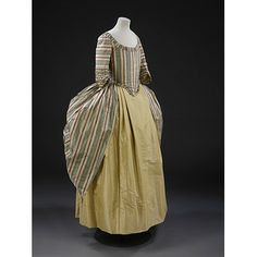 Robe a la polonaise, British, ca. 1775. Made of silk lined with linen. This gown is an example of a new style introduced in the 1770s called a polonaise. Using buttons and loops, the skirt of the gown was draped up to create the swathed effect at the back shown here. Also popular during this decade were a range of striped fabrics, often in a complex arrangement of colours with both sharp and shaded edges, as seen in this example.    Draping the skirt was not only a fashionable option. It also...