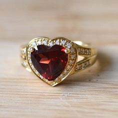 Estate 14 karat yellow gold 3.25 carat heart shaped garnet ring with diamonds. This ring includes 34 round diamonds at 0.34 carat total weight SI1 clarity G-H color. Size 7.