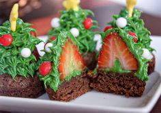 Christmas tree desserts: bite-sized brownie rounds topped with an upside down hulled strawberry iced with green pull-out stars and decorated with Christmas candy bits.