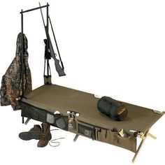 """Cabela's Heavy-Duty Army Cot 4-Pc. Combo: •Cot built to military specifications •Convenient cot tree for hanging gear •Nightstand keeps camp essentials close by •Carry bag included Sleeping area: 77""""L x 28""""W. Weight capacity: 500-lb. Included: •Heavy-Duty Army Cot. •Cot-Side Nightstand™ and the Cot Tree™. •Carrying bag."""
