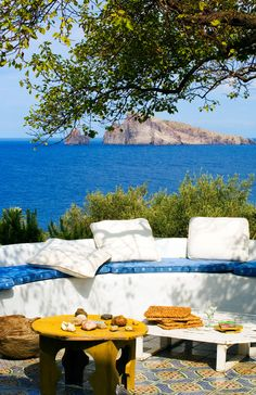 white built-in outdoor seating with blue cushions with view of the mediterranean